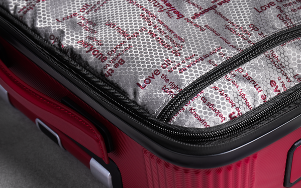The interior of (Montblanc M) RED travel luggage patterned with quotes.